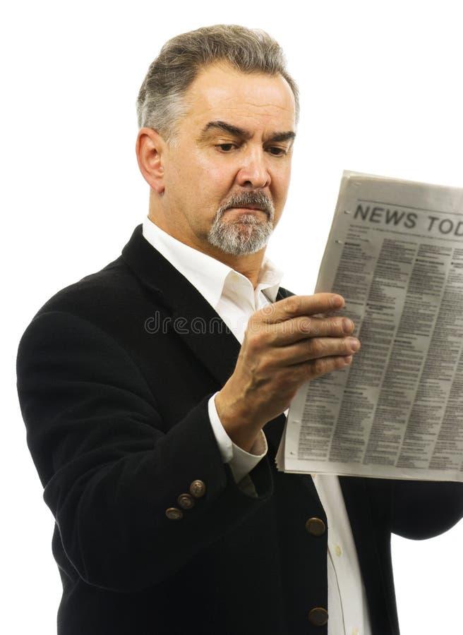 De mens leest krant met ernstige blik op gezicht stock fotografie
