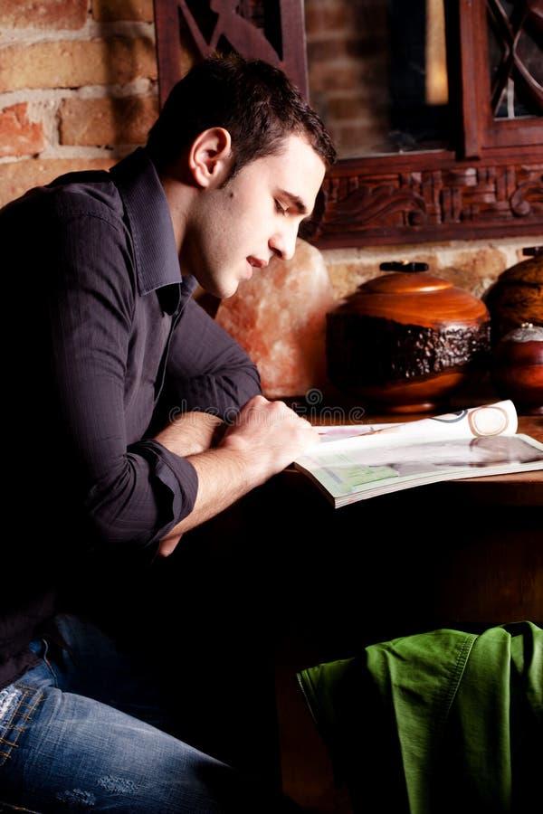 De mens leest tijdschrift stock foto's