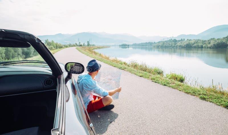 De mens leest wegenkaartzitting dichtbij zijn cabriolet op schilderachtige mo stock foto's