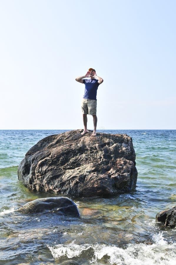 De mens liep op een rots in oceaan vast stock afbeelding