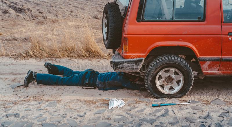 De mens ligt onder een 4x4-auto op een landweg stock foto