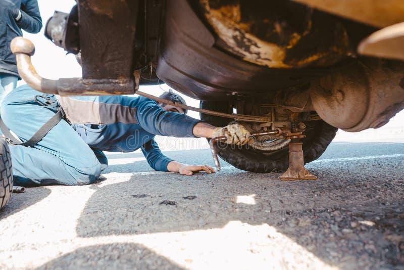 De mens ligt onder een 4x4-auto op een landweg royalty-vrije stock afbeeldingen