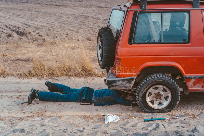 De mens ligt onder een 4x4-auto op een landweg royalty-vrije stock fotografie