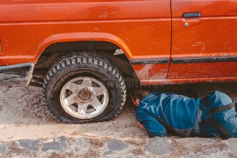 De mens ligt onder een 4x4-auto op een landweg stock afbeelding