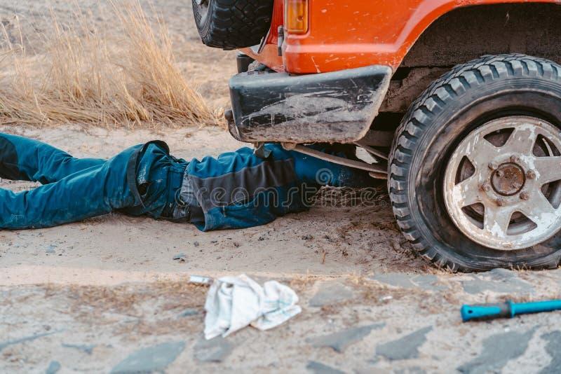 De mens ligt onder een 4x4-auto op een landweg stock foto's
