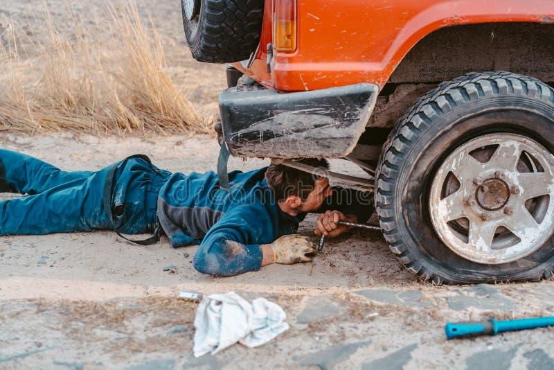 De mens ligt onder een 4x4-auto op een landweg stock fotografie