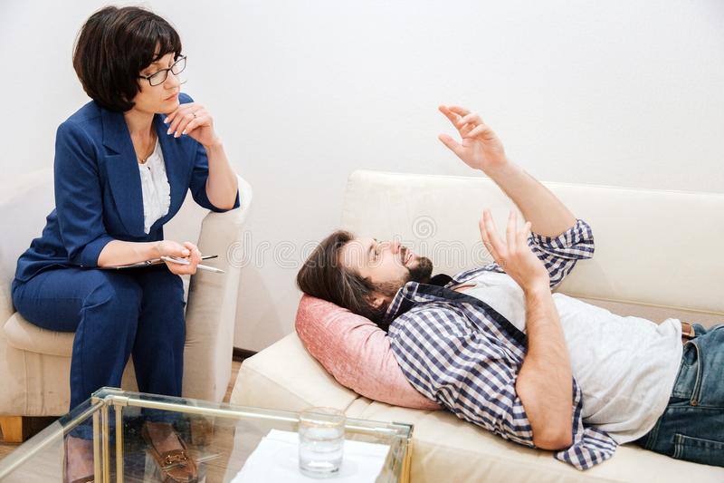 De mens ligt op bank en golft met zijn handen Hij is op het ogenblik vrij emotioneel Hij spreekt aan therapeut Woman stock fotografie