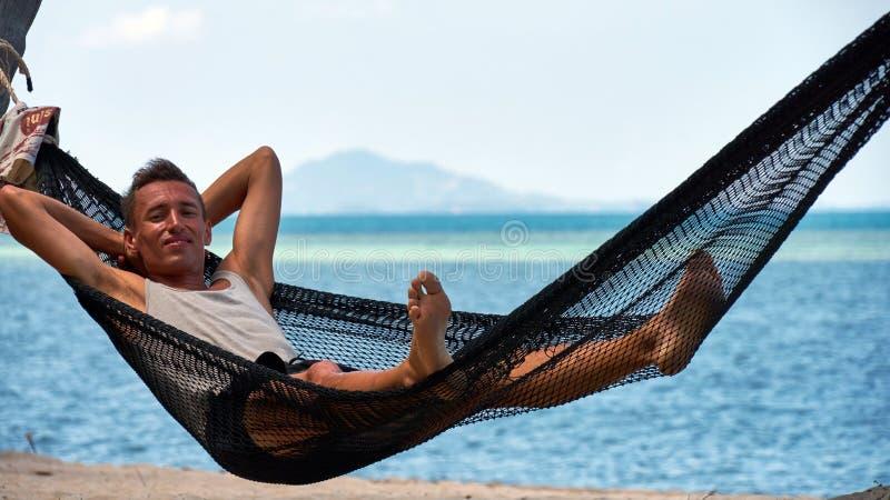De mens ligt op een hangmat stock afbeelding