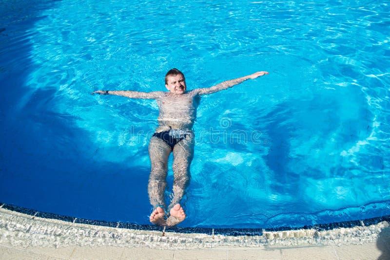 De mens ligt op oppervlakte van water in het zwembad stock afbeeldingen