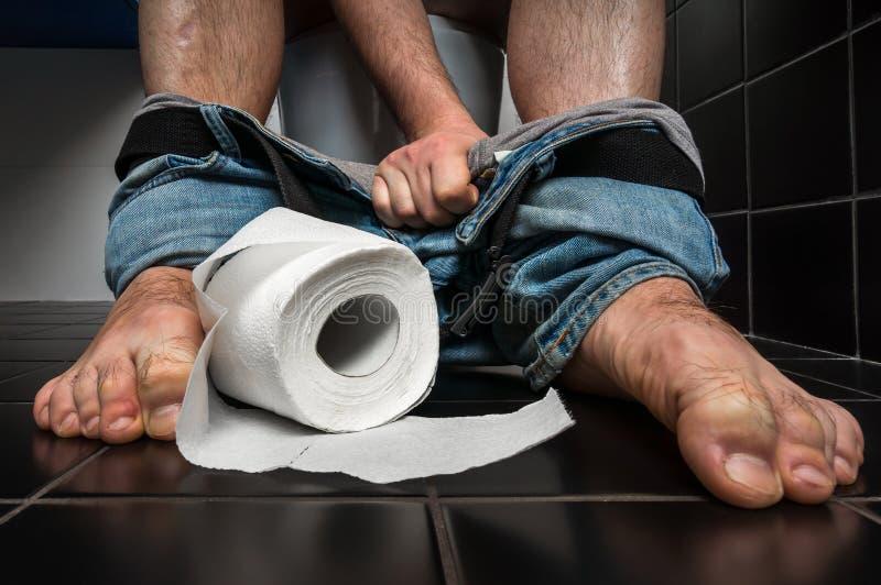 De mens lijdt aan diarree zit op toiletkom royalty-vrije stock foto