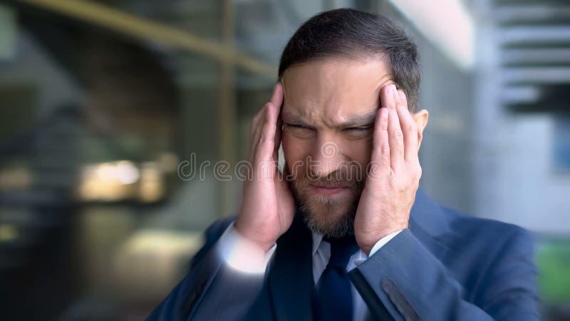 De mens lijdt aan hoofdpijn, masserend tempels, migraine het duizelige effect, omhoog sluit stock foto's