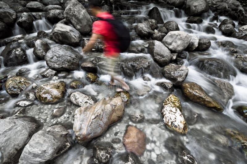 De mens loopt op Bergstroom stock afbeelding