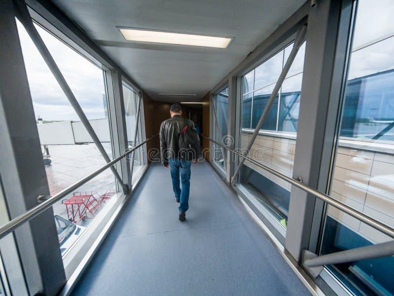 De mens in luchthavenpoort inschepen of de straal die overbrugt of jetway of airbridge aan een vliegtuig stock foto's