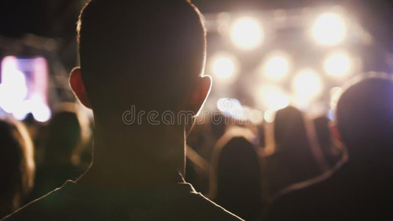 De mens luistert het rotsoverleg in stadion stock foto