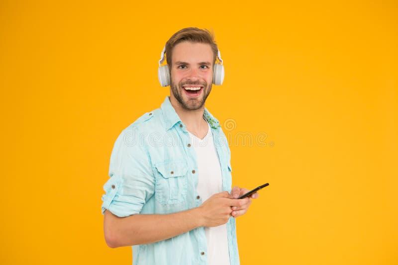 De mens luistert muziek moderne hoofdtelefoons en smartphone Let op vrij Krijg het abonnement van de muziekfamilie Geniet muziek  royalty-vrije stock afbeeldingen