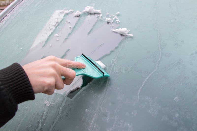 De mens maakt bevroren autoraam met ijsschraper schoon royalty-vrije stock afbeelding