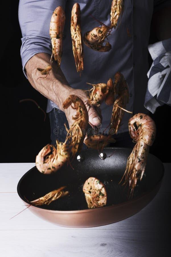 De mens maakt het springen garnalen in de pan stock fotografie