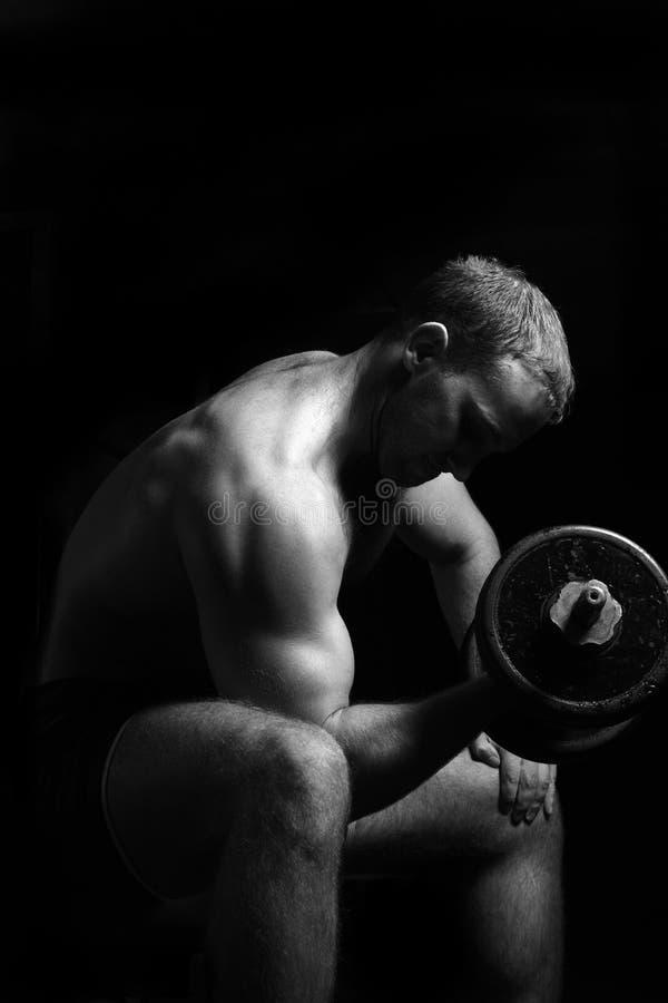 De mens maakt oefeningen met barbell stock fotografie