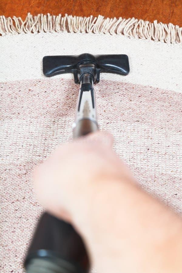 De mens maakt tapijt met stofzuiger schoon stock foto's