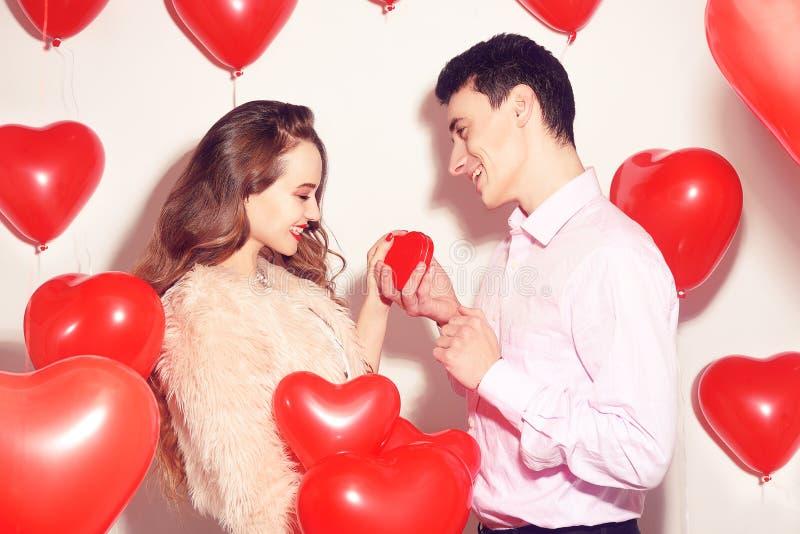 De mens maakt tot heden aan zijn mooi liefjemeisje De valentijnskaartdag van de minnaar Valentine Couple De mens geeft aan zijn m stock afbeelding
