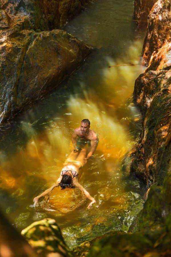 De mens met actiecamera registreert zijn meisje die in een wate zwemmen stock afbeeldingen