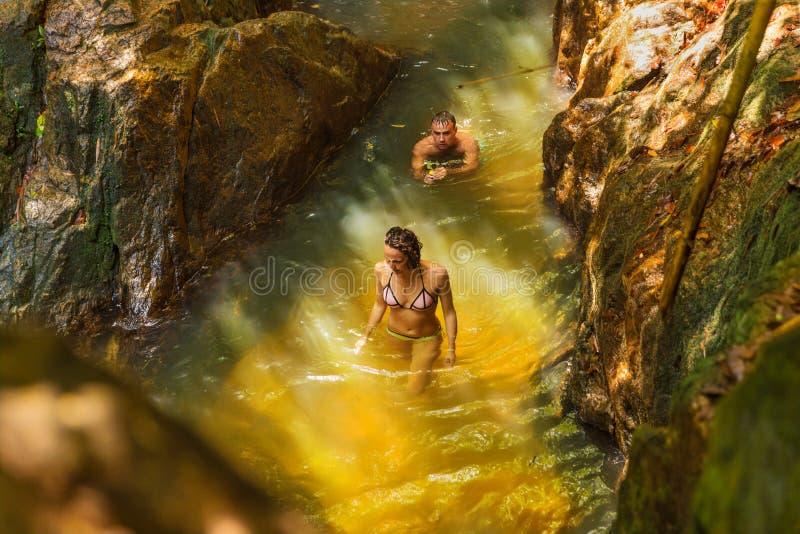De mens met actiecamera registreert zijn meisje die in een wate zwemmen stock foto's