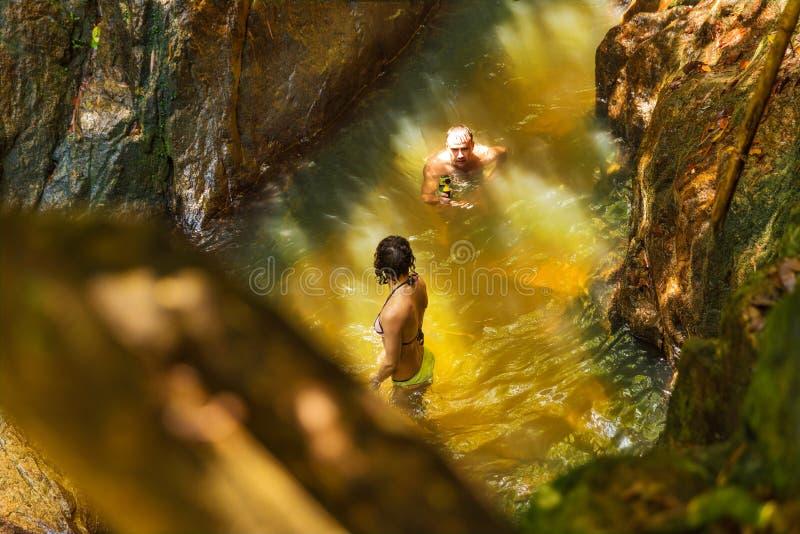 De mens met actiecamera registreert zijn meisje die in een wate zwemmen stock foto