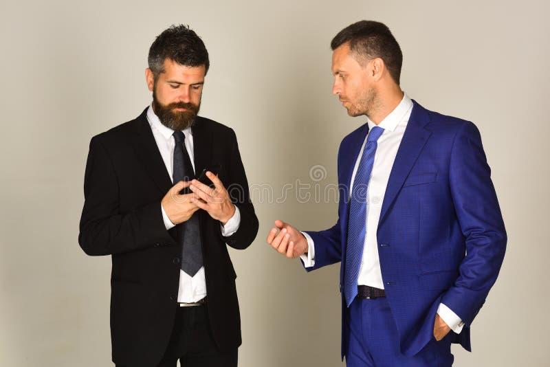 De mens met baard en geconcentreerd gezicht houdt telefoon royalty-vrije stock foto's