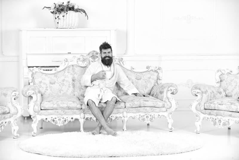De mens met baard en snor geniet van ochtend terwijl het zitten op ouderwetse luxebank Mens vrolijk in badjasdranken royalty-vrije stock foto's