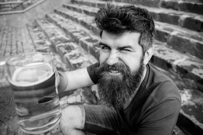 De mens met baard en snor houdt glas met bier terwijl op steentreden zit, defocused Kerel die rust met trekking hebben royalty-vrije stock fotografie