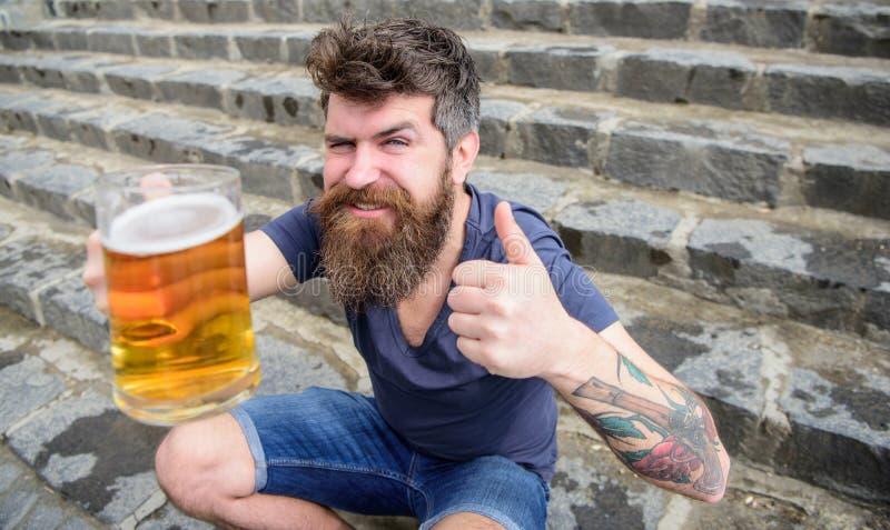 De mens met baard en snor houdt glas met bier en toont duim, de achtergrond van steentreden Kerel die rust met koude hebben royalty-vrije stock fotografie