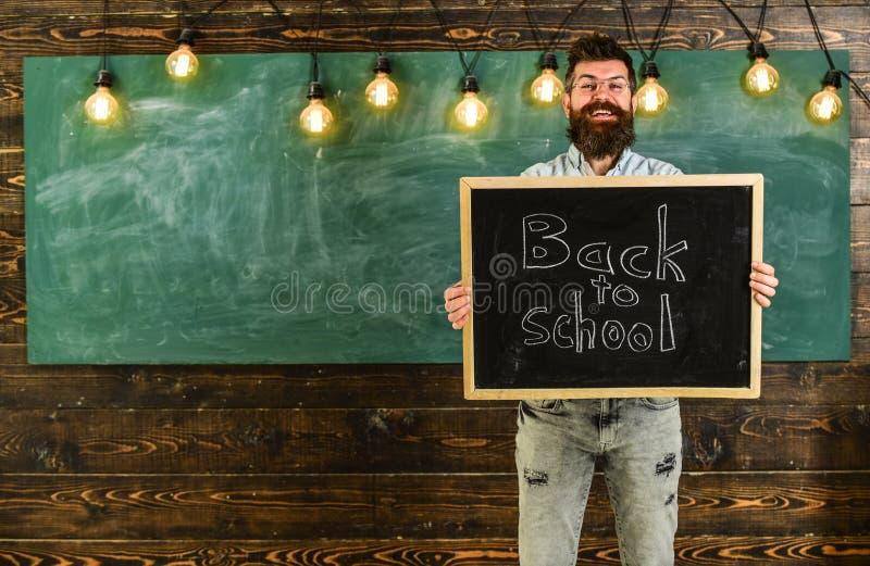 De mens met baard en snor op vrolijk het glimlachen gezicht heet studenten, bord op achtergrond welkom Leraar in oogglazen royalty-vrije stock foto