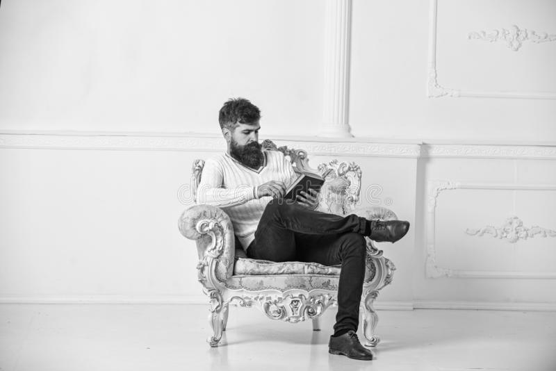 De mens met baard en snor zit bij leunstoel en de lezing, witte muurachtergrond Kenner van literatuurconcept stock afbeelding