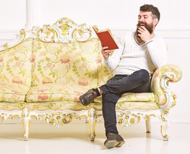 De mens met baard en snor zit op barokke stijlbank, houdt boek, witte muurachtergrond Kerel die oud boek lezen met royalty-vrije stock afbeelding