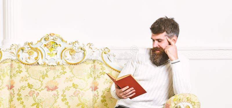 De mens met baard en snor zit op barokke stijlbank, houdt boek, witte muurachtergrond Macho op het glimlachen gezicht stock fotografie