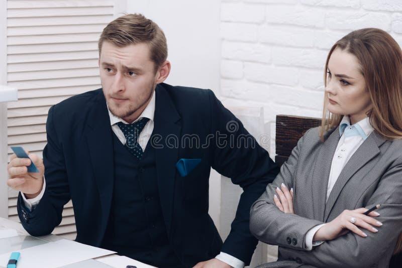 De mens met baard houdt plastic bezoekkaart Het introduceren van concept Partners of zakenman op vergadering, bureau stock afbeeldingen