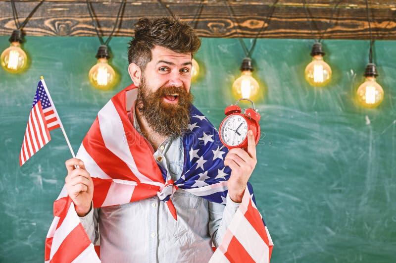 De mens met baard op vrolijk gezicht houdt vlag van de V.S. en klok, bord op achtergrond, exemplaarruimte Amerikaanse leraar met stock afbeelding