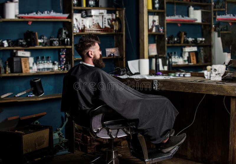 De mens met baard met zwarte kaap wordt behandeld zit als kappersvoorzitter voor spiegel die Mens met baardcliënt van hipster stock foto