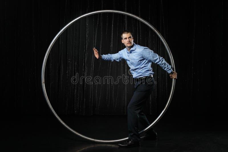 De mens met cirkel bekijkt zijn horloge bij zwarte achtergrond royalty-vrije stock afbeelding
