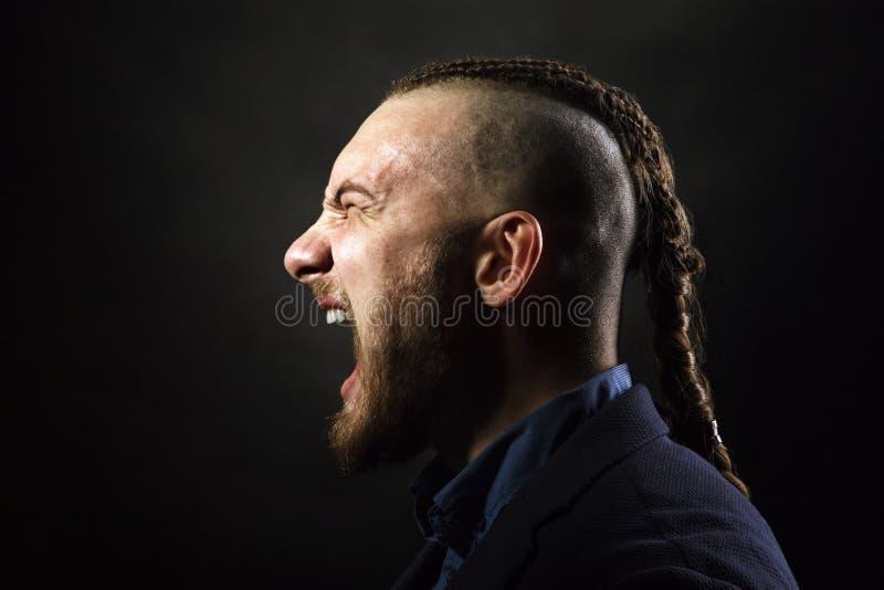 De mens met dreadlocksschreeuwen in een woede, kijkt als een Viking, Iroquois kapsel royalty-vrije stock foto