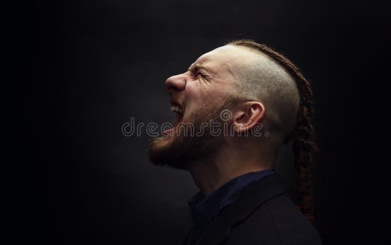 De mens met dreadlocksschreeuwen in een woede, kijkt als een Viking, Iroquois kapsel royalty-vrije stock fotografie