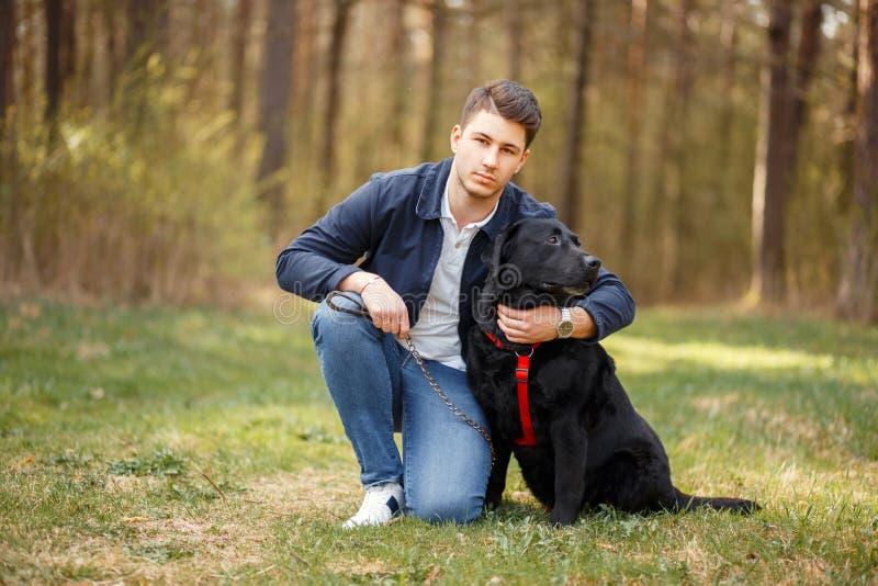 De mens met een hond loopt in aard op een de lentedag royalty-vrije stock foto's
