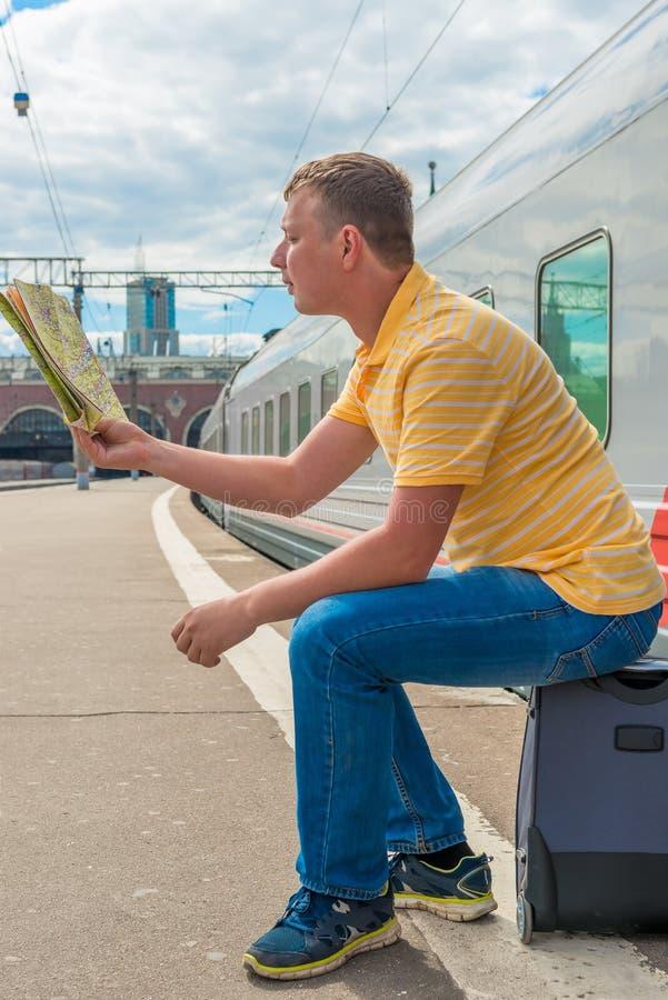 De mens met een kaart en een koffer wacht trein royalty-vrije stock fotografie