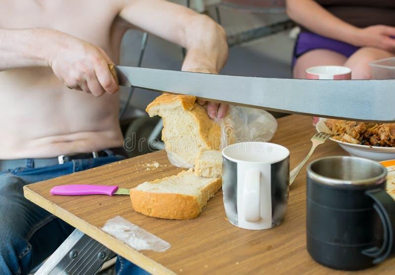 De mens met een naakt torso, die bij de lijst zitten, snijdt een brood van brood met een reusachtig mes stock foto