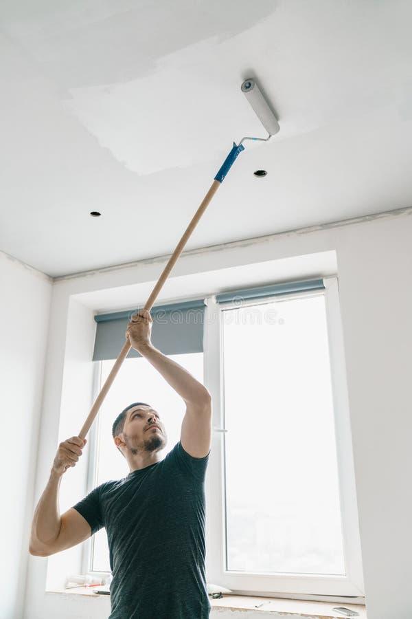 De mens met een rol in zijn hand op een lange stok schildert het plafond in grijs bij het venster royalty-vrije stock afbeelding