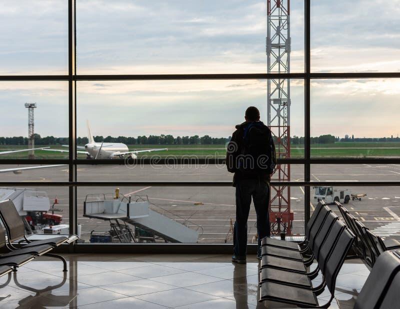 De mens met een rugzak bekijkt de vliegtuigen royalty-vrije stock afbeeldingen