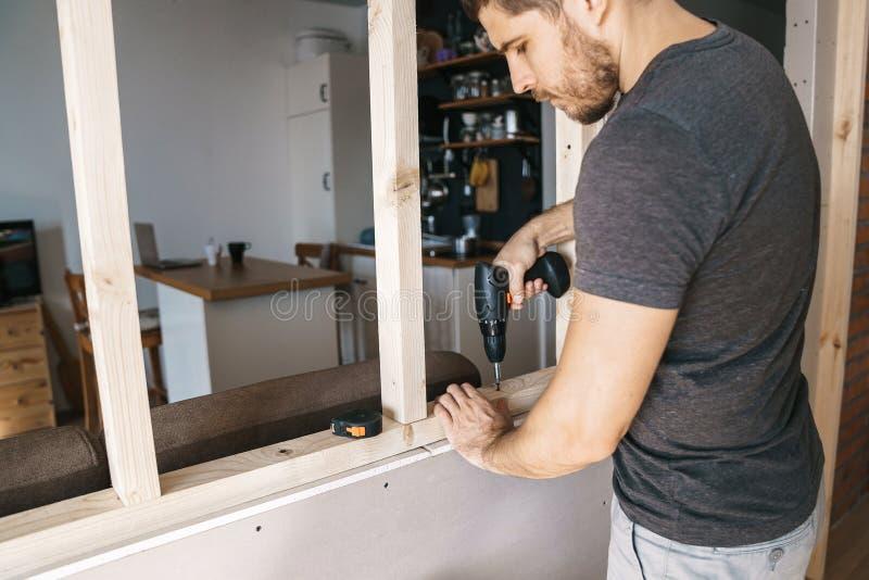 De mens met een schroevedraaier in zijn hand bevestigt een houten structuur voor een venster in zijn huis Reparatie zelf stock foto