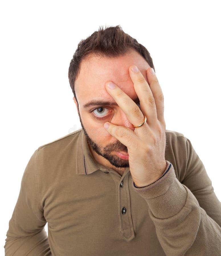 De mens met een wanhopige uitdrukking met dient gezicht in stock afbeelding