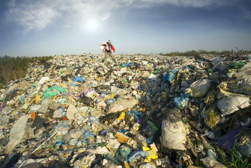 De mens met een zak neemt afval op stock afbeeldingen