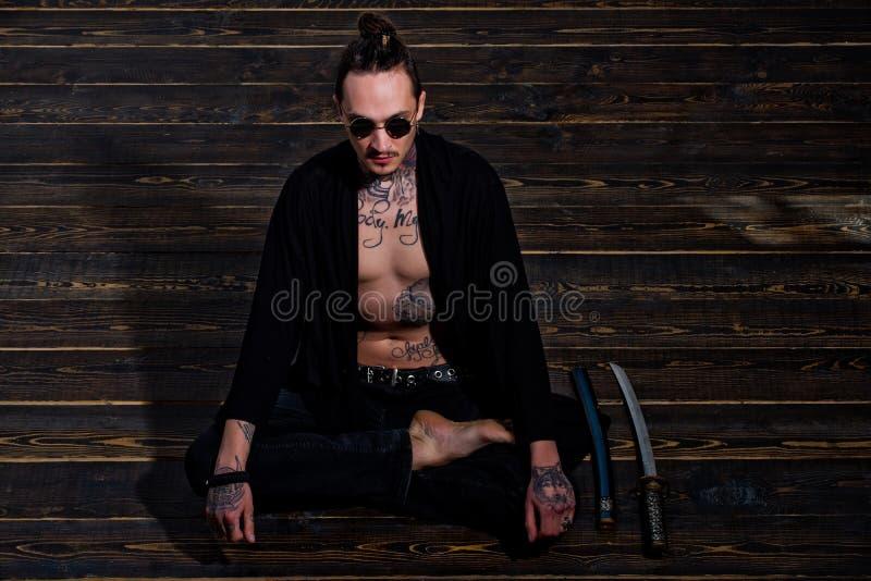 De mens met getatoeeerde torsozitting in meditatie stelt met zwaarden stock fotografie